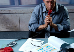 businessman-thinking-while-holding-telephone