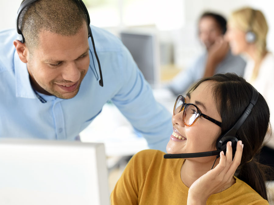 call center team leader coach assisting customer service rep at works