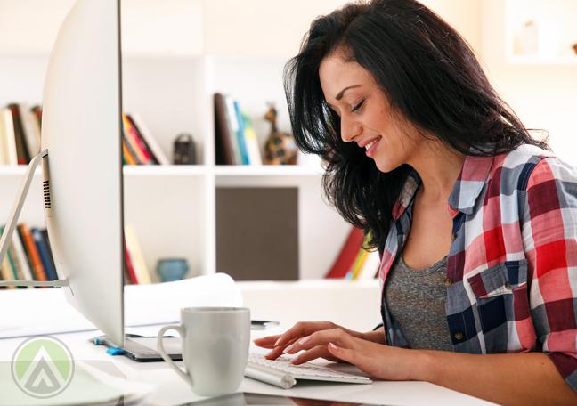 female-blogger-working-on-Mac-computer-with-mug-of-coffee