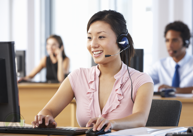 female-Asian-call-center-agent-attending-to-a-customer-with-coworkers-at-the-back
