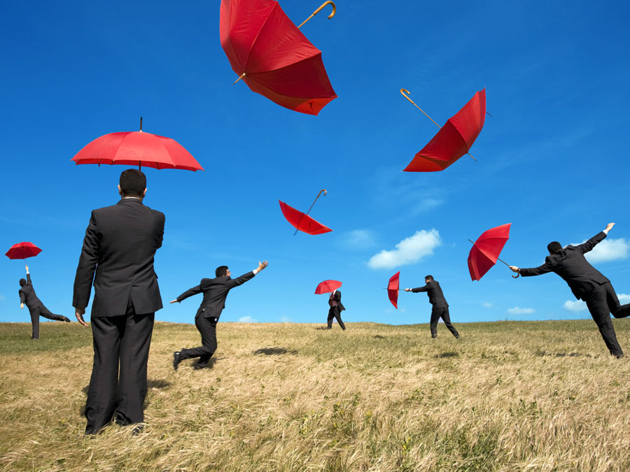 businessmen difficulty holding red umbrellas blown by wind
