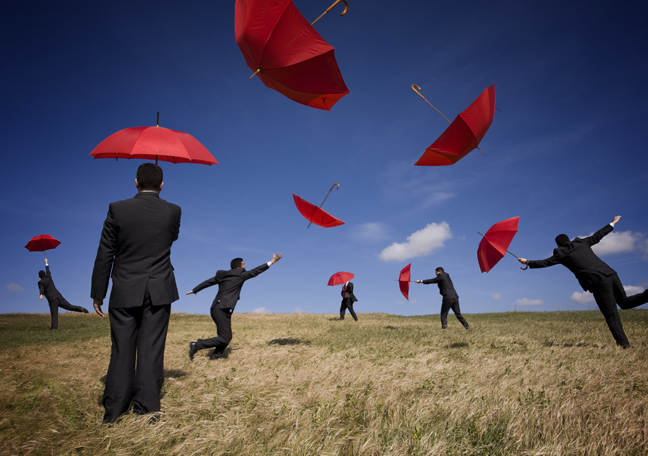 businessmen running after red umbrellas in open grassy field