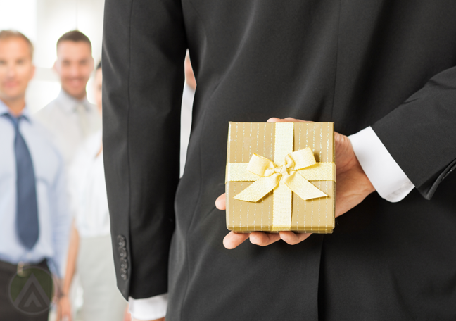 gift in gold wrap held by businessman on back hidden from employees