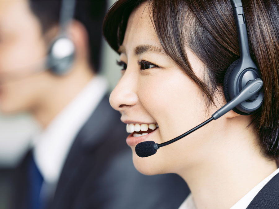 smiling japanese call center agent assisting caller over the phone