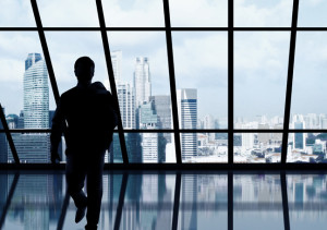 businessman-looking-at-the-skyscraper-outside-the-office-window