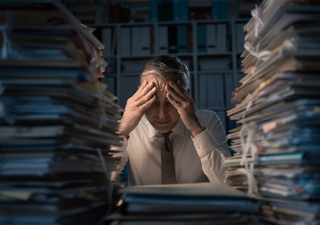 content moderation agents with a headache surrounded by piles of paper in the dark BPO office