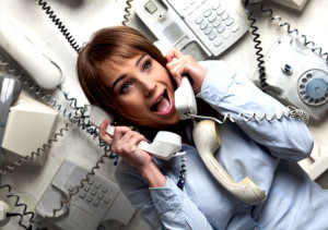 anxious-female-agent-holding-lots-of-wired-telephones