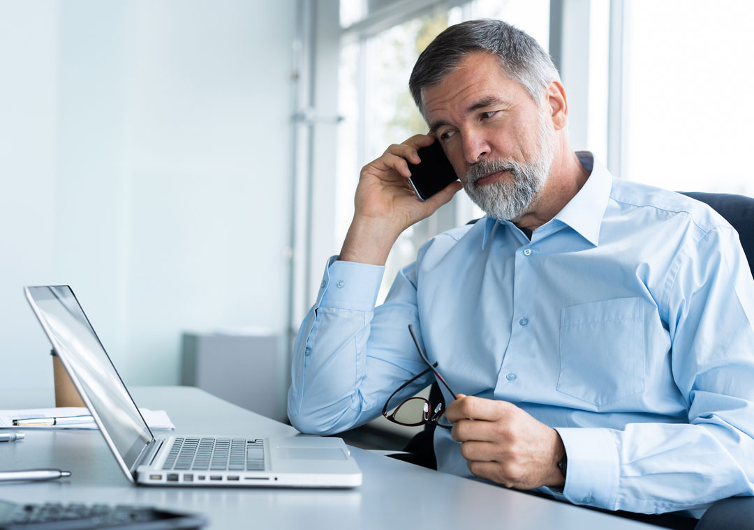 businessman on the phone talking to customer service using laptop to answer survey