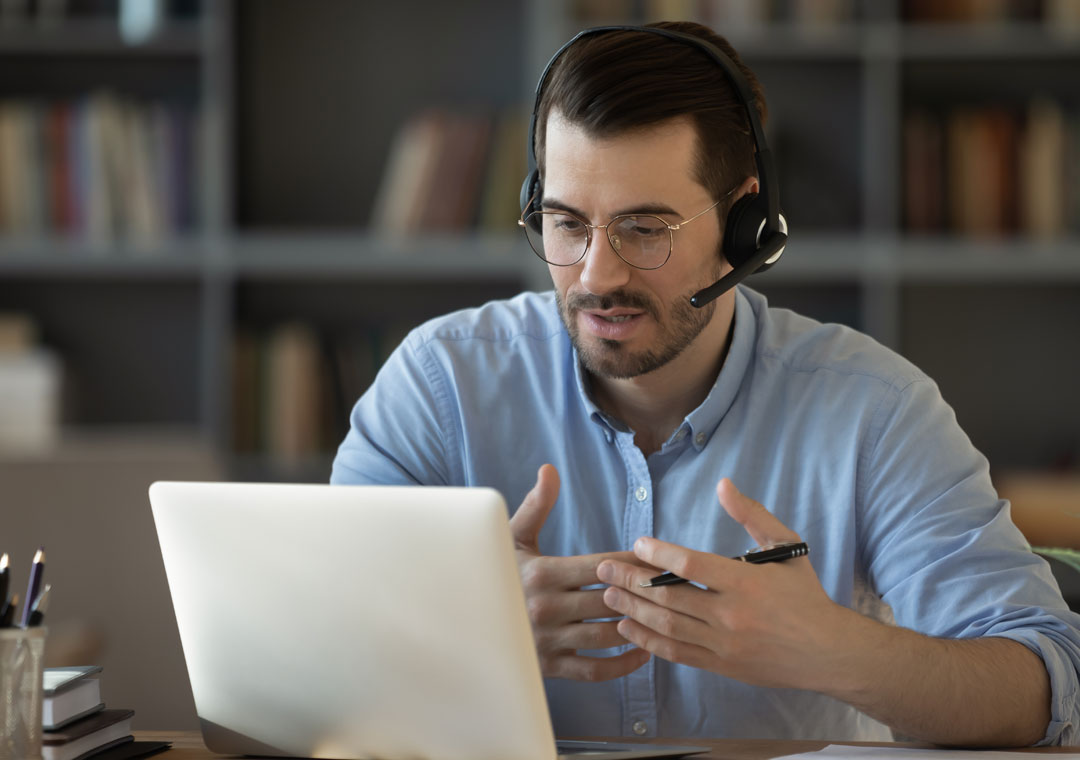 customer care agent sppeaking to caller looking at laptop