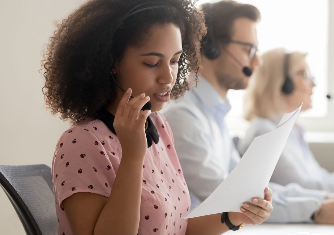 customer support agent in call center reading quality assurance scripting
