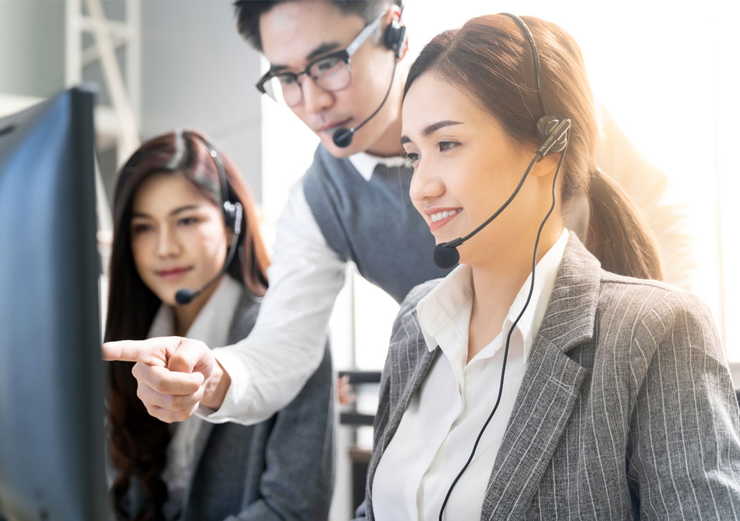 team leader listening to customer service call center calls for quality assurance