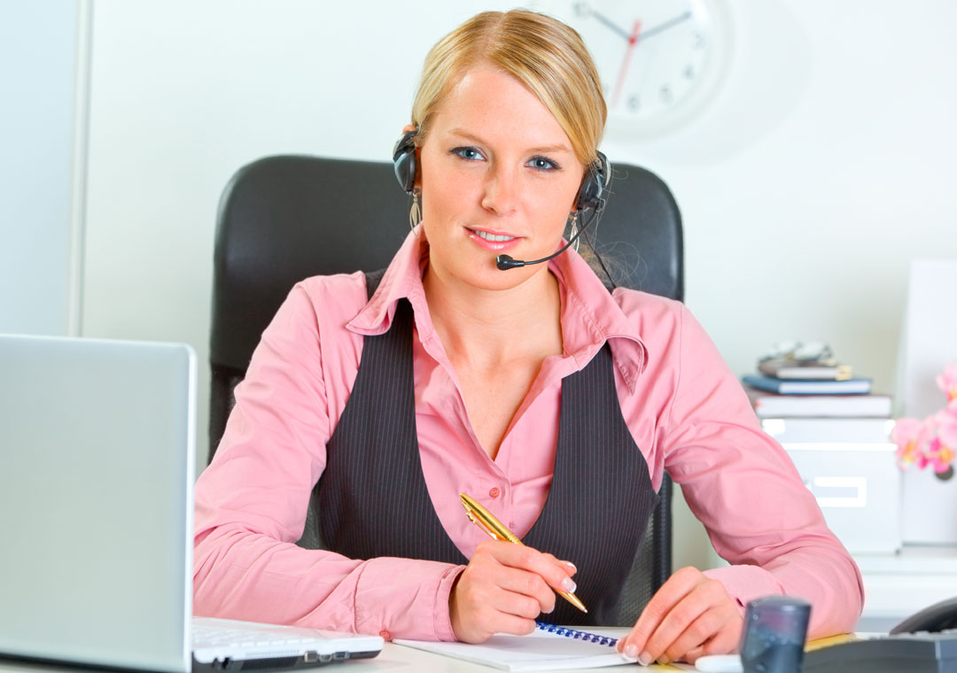 live chat support agent smiling with laptop writing on paper