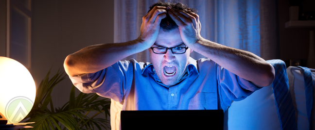 man-in-glasses-panicking-in-front-of-laptop-in-dark-room