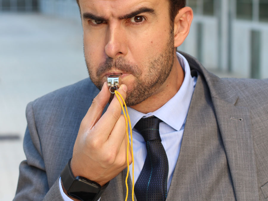 businessman using policeman whistle