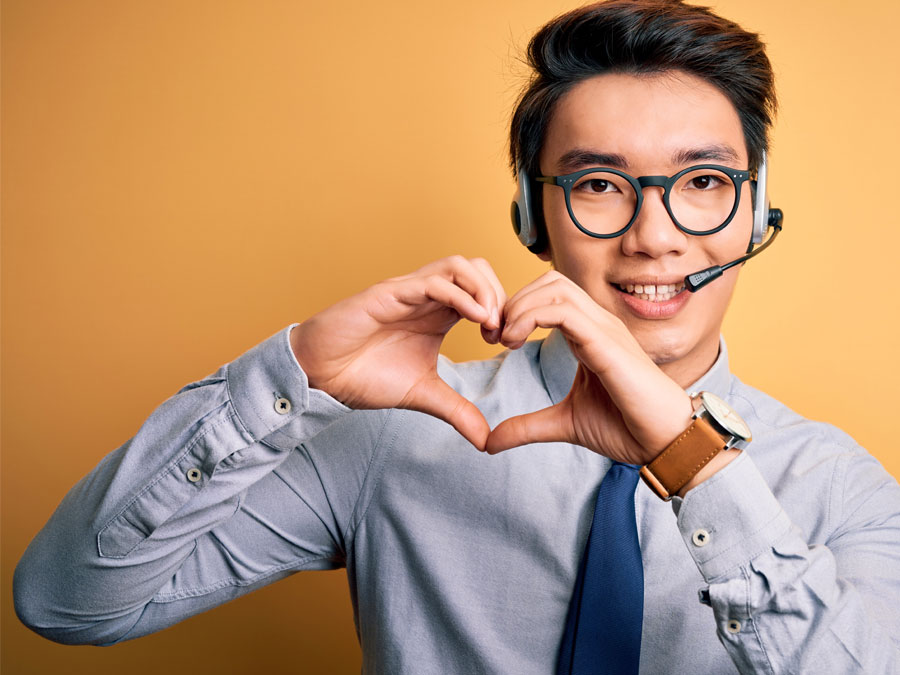Asian customer service agent in call center making hearts