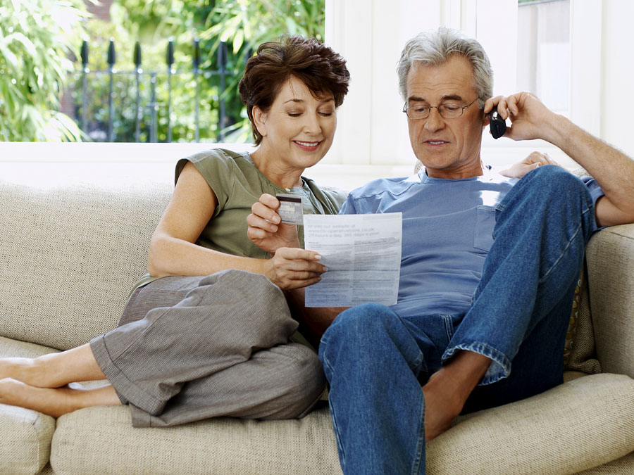 baby boomers elderly couple on couch using phone looking at catalogue