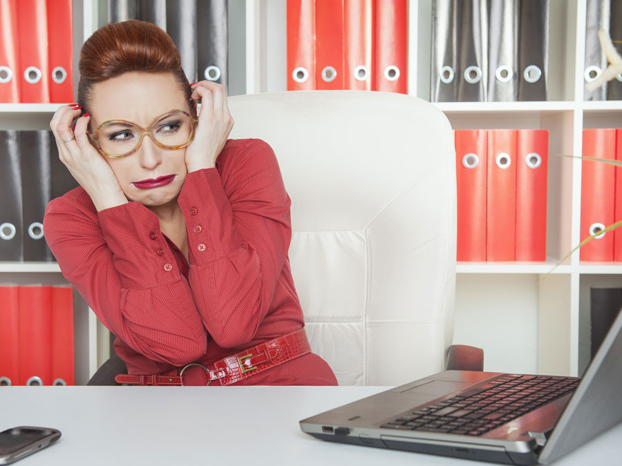 business executive in red scared of laptop