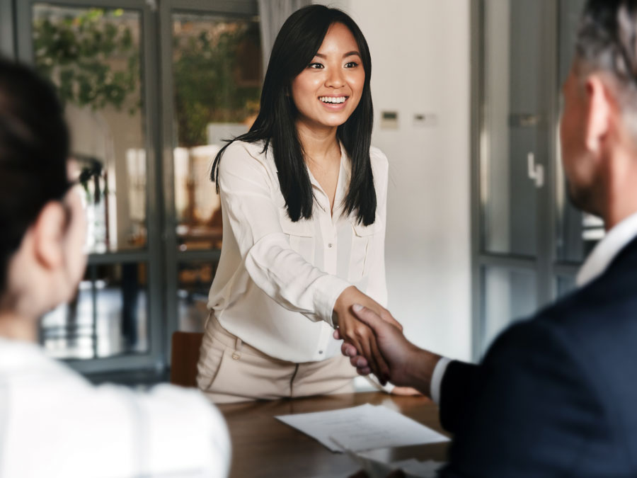 job applicant shaking hands with recruitment team