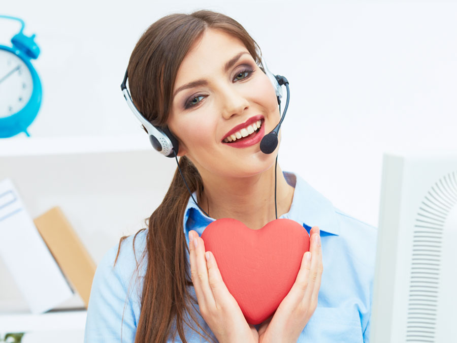 Smiling customer service agent holding heart