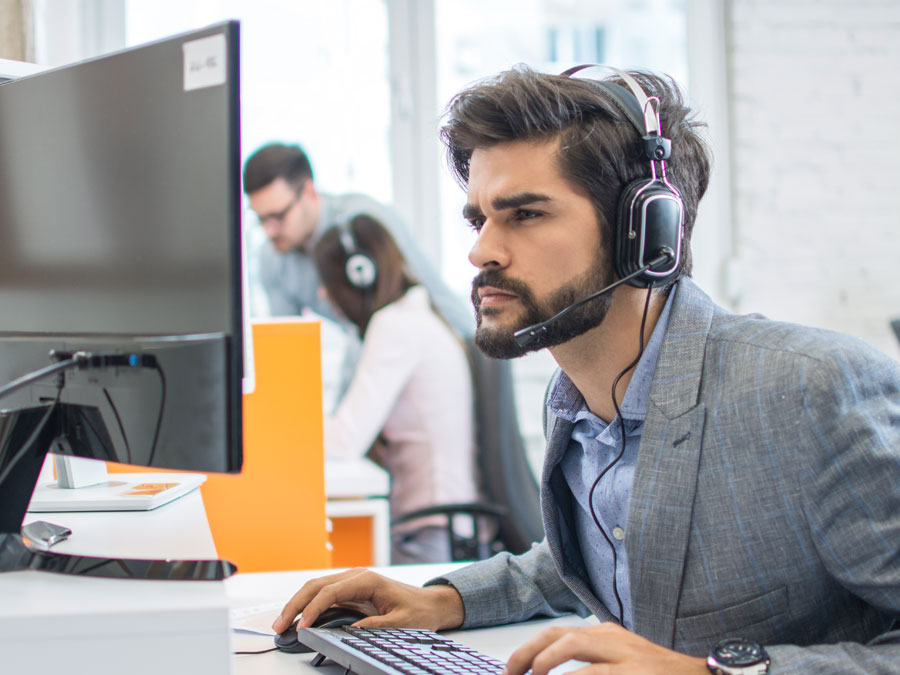 customer service agent in call center looking intently at computer screen