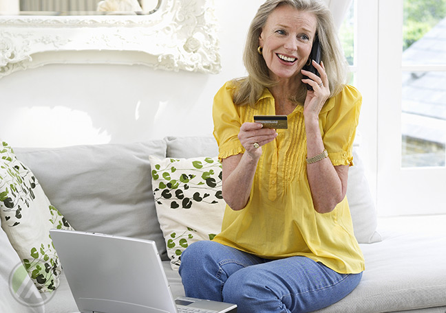 elderly-woman-on-the-phone-holding-a-credit-card-and-facing-a-laptop