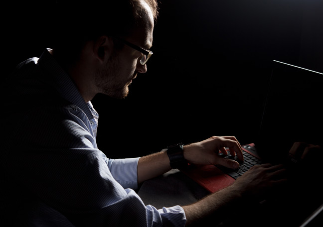 hacker-posing-as-employee-with-laptop-in-dark