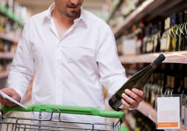 male-shopper-holding-wine-bottle-grocery