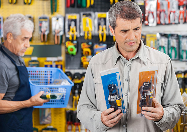 man-in-hardware-store-comparing-products-on-his-own-with-store-staff-in-the-background