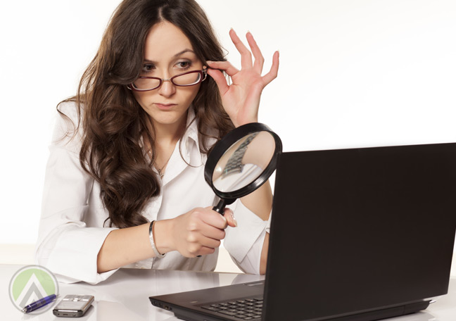 woman-in-glasses-looking-at-laptop-with-magnifying-lens