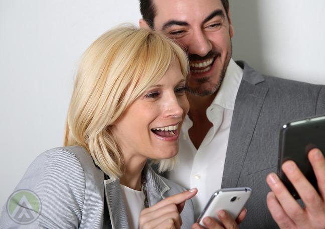 couple-smiling-laughingat-smartphones