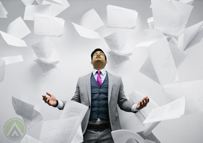 young-male-employee-surrounded-flying-papers