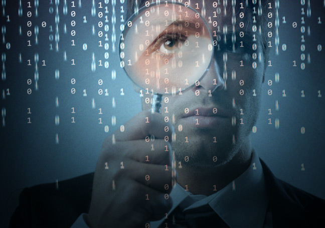 businessman-with-magnifying-lense-looking-at-computer-codes-and-text