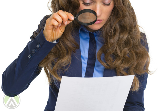 female-employee-in-blue-looking-closely-at-document-with-magnifying-lens