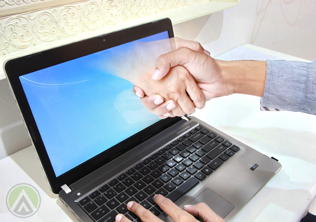 hand-reaching-out-of-laptop-to-shake-businessman-hands
