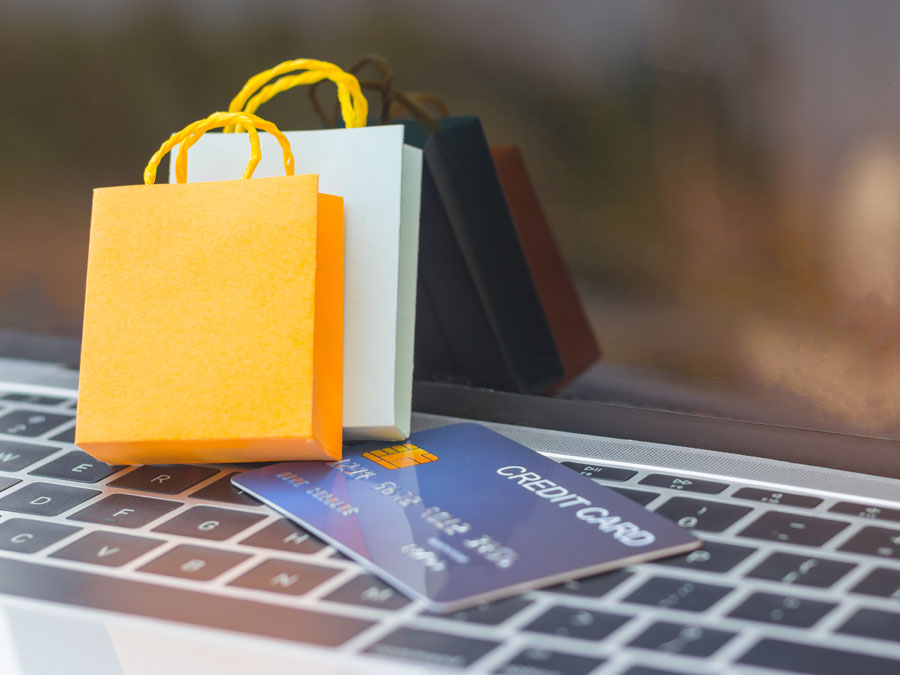 tiny shopping bags on credit card on laptop