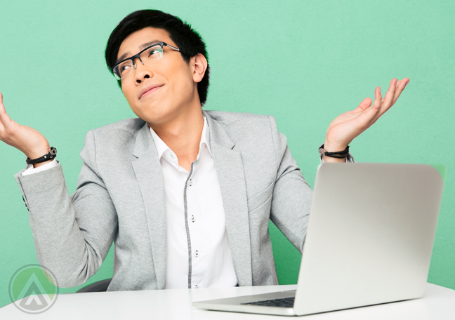 asian-male-employee-in-glasses-shrugging-in-front-of-laptop-computer