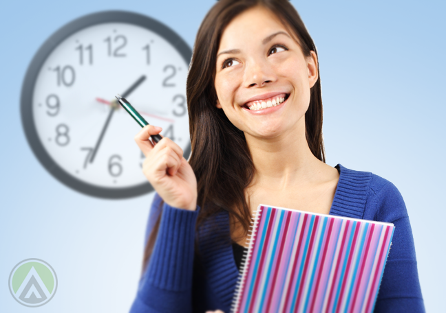 brunette-woman-smiling-holding-notebook-pointing-pen-to-wall-clock