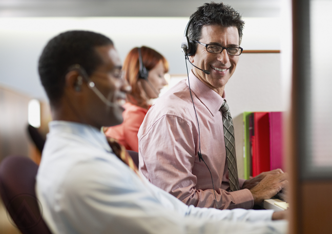 male-customer-support-agent-in-glasses-surrounded-by-diverse-call-center-coworkers