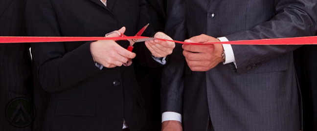 male-female-business-executive-cutting-red-ribbon