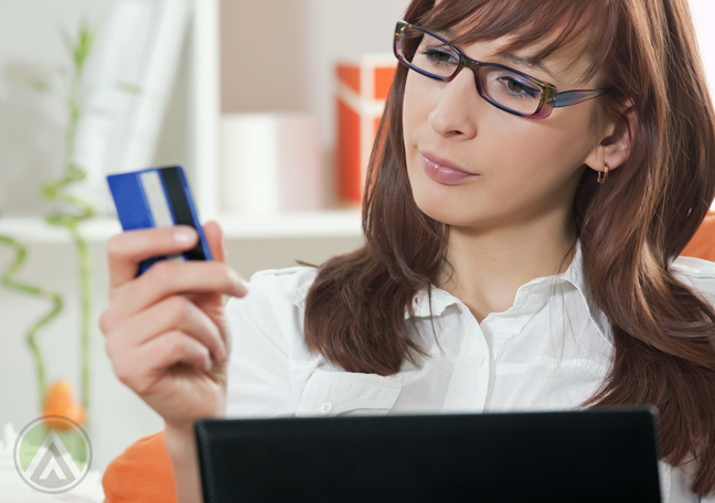 woman-in-glasses-in-front-of-laptop-staring-at-credit-card