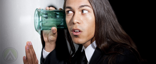 young-business-employee-with-long-hair-eavesdropping-on-wall-with-glass