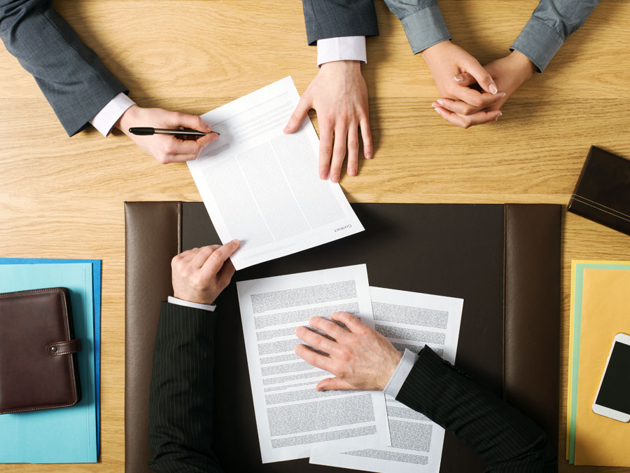 executive team inspecting studying outsourcing contracts