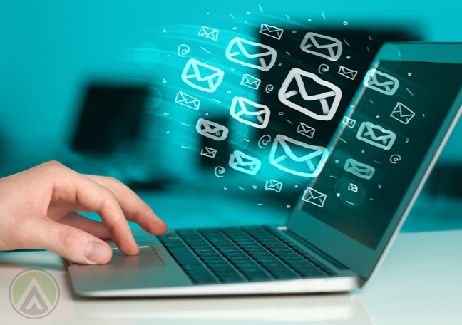 hand-using-laptop-with-email-icons-flying