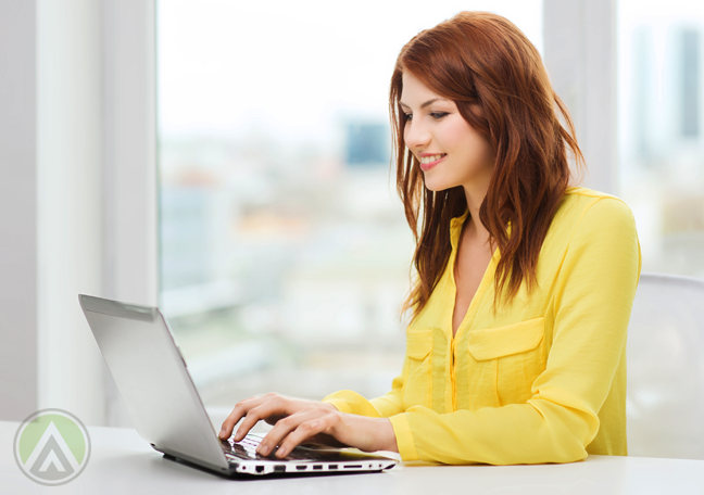 read-haired-young-woman-in-yellow-shirt-using-laptop