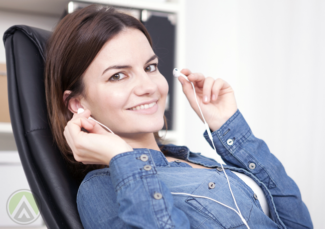 smiling-brunette-sitting-in-comfy-chair-about-to-wear-earphones