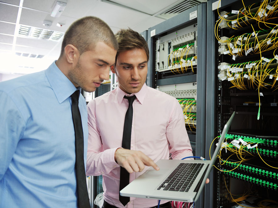 IT helpdesk staff in server room checking equipment