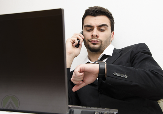 annoyed-businessman-in-phone-call-looking-at-watch-waiting-by-laptop