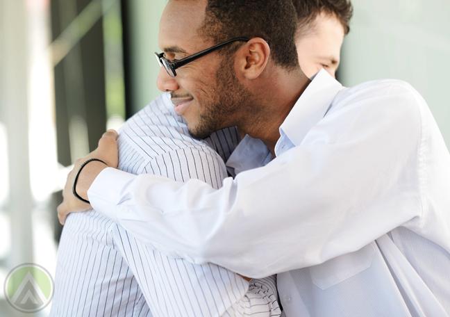 diverse businessmen-hugging