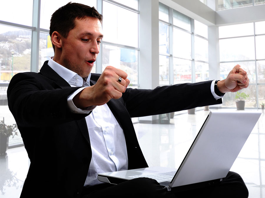 excited businessman speaking with outsourcing live chat on laptop