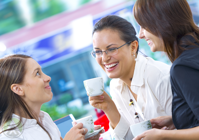 female-business-associates-laughing-chatting-over-coffee